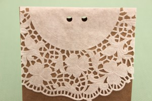 Two Holes Punched Into the Top of the Doily-Lined Paper Bag